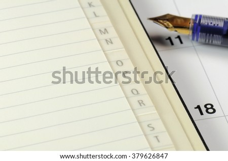 phone book and calendar with fountain pen - stock photo