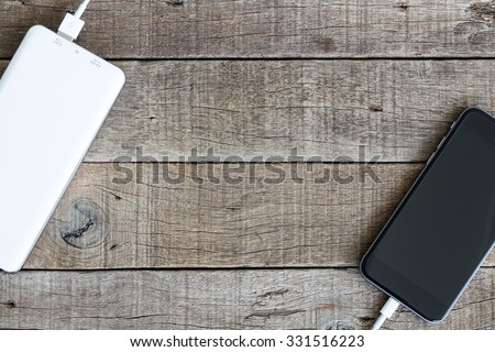 phone charging with power bank on wood background - stock photo