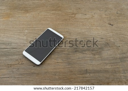 Phone display crack isolated on wooden table - stock photo