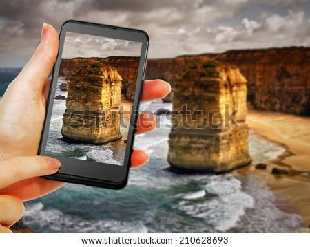 phone in hand  taking 12 apostles picture - stock photo