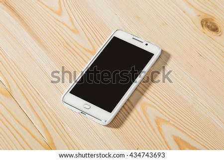Phone lying in the interior on the wooden table - stock photo
