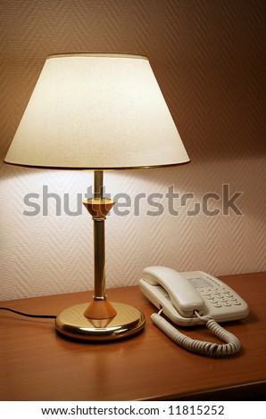 Phone on a table near to a lamp - stock photo