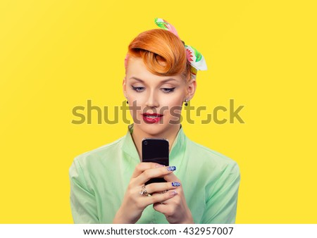 Phone Texting. Beautiful attractive pinup girl playing on cellphone retro vintage 50's style isolated yellow background Positive human face expression emotion feeling reaction perception body language - stock photo