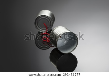 phone toy from a tin can lying on a smooth black polished table - stock photo
