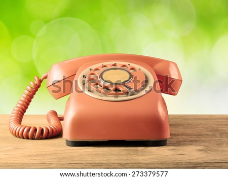 Phone vintage on table wood and green bokeh background - stock photo