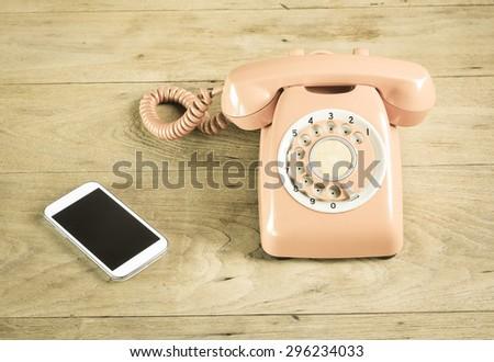 Phone vintage on wood table - stock photo