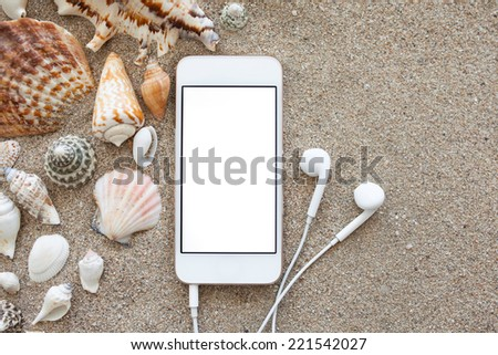 phone with isolated screen and headphones lying on the sand with shells - stock photo