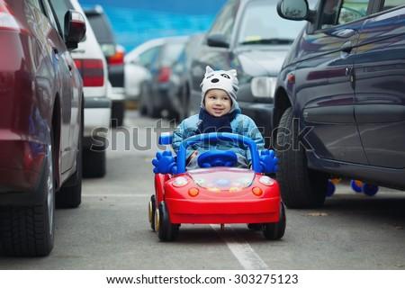 photi of cute little boy on supermarket parking - stock photo