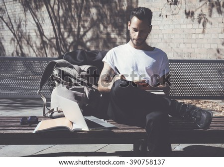 Photo bearded artist wearing white tshirt sitting city park and draws. Studying at the University, working project. Books, generic design laptop, backpack bench.  Horizontal - stock photo