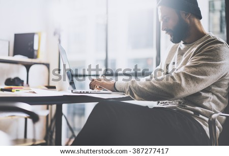Photo bearded graphic designer working with new project modern loft. Generic design notebook on wood table.  Analyze plans, papers, hands keyboard. Blurred background, film effect - stock photo