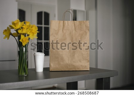 Photo blank: disposable bag of kraft paper on a wooden table and cup of coffee - stock photo