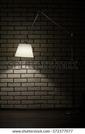 photo by floor lamp in brick room  - stock photo