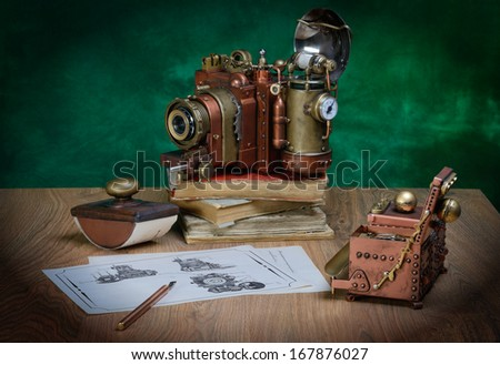 Photo camera and drawing on a wooden table. Style Steampunk. - stock photo
