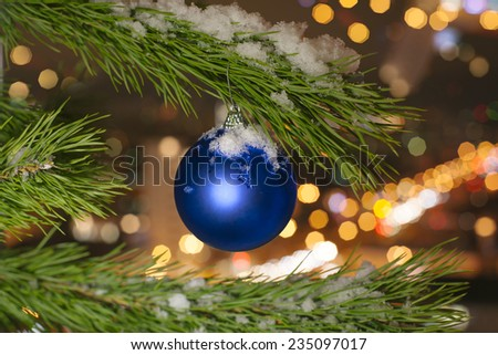 Photo Christmas ball on a Christmas tree branch on a background of the night city lights and - stock photo