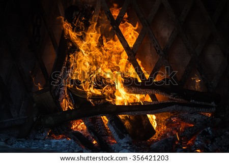 Photo closeup of fire lit burning flashing wood kindled orange tongues of flame live embers coal cinders on fireplace background, horizontal picture - stock photo