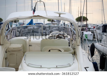 Photo closeup of modern white ocean-going launch motor boat yacht at moorage on sea port terminal background, horizontal picture - stock photo