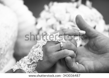 Photo closeup of newlyweds groom holding hand of bride with wedding rings rites of matrimony black and white on blurred bridal bouquet background, horizontal picture  - stock photo