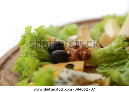 Photo closeup of various types of gourmet cheese slices triangles with mold green salad black olives and walnuts on wooden platter over blurred background, horizontal picture - stock photo