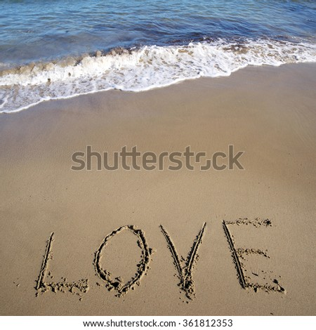 Photo closeup of word love written on beautiful wet beige beach sea marine grained sand against blue waves with splashes white spindrifts running on seashore on seascape background, square picture - stock photo