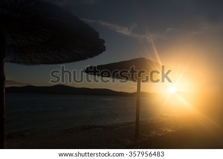 Photo closeup with sun spot of seascape with beach umbrellas for sun protection in line at seashore silhouetted against sunset background, horizontal picture - stock photo