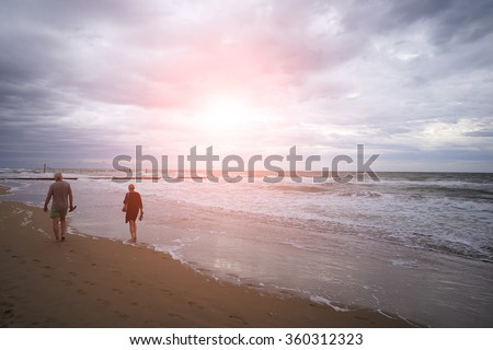 Photo closeup with sun spot of two people walking barefoot at seashore beach on wet marine sand sea with blue waves and white spindrifts running on seascape background, horizontal picture  - stock photo