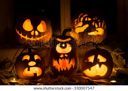 Photo composition from five pumpkins for Halloween. Jack, hands, crying, a Cyclops and frightened pumpkins against autumn leaves and candles - stock photo