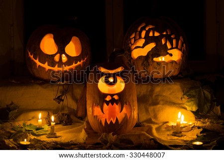 Photo composition from three pumpkins on Halloween. Jack, terrible hands, and a Cyclops of pumpkin against an old window, leaves and candles. - stock photo