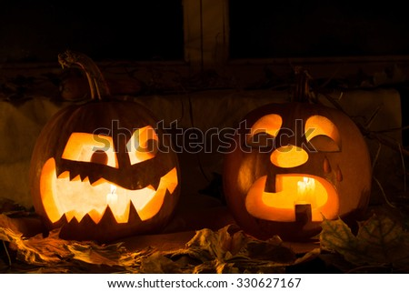 Photo composition from two pumpkins on Halloween. Embittered and tear-stained pumpkins stand against an old window, leaves and candles. - stock photo
