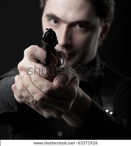 photo dark man pointing a gun looking at the camera - stock photo