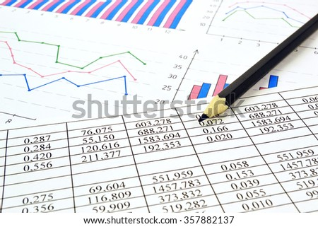 Photo diagrams graphs and numerals in the table on the paper - stock photo