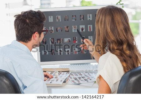 Photo editor pointing at computer while working on computer with a colleague - stock photo