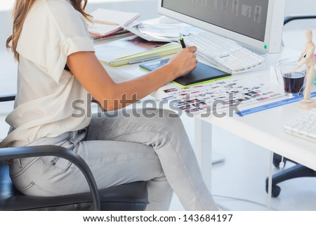 Photo editor pointing using graphics tablet in her office - stock photo
