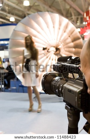 Photo exhibition concept. Man shoot a film about posing model. - stock photo