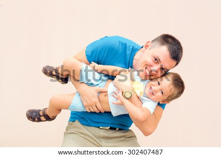 Photo father and his young son. Father playing with his son. - stock photo