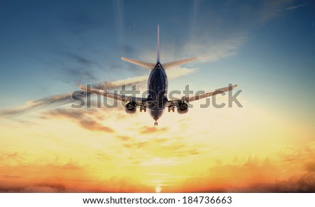 Photo flying airplane at sunset - stock photo