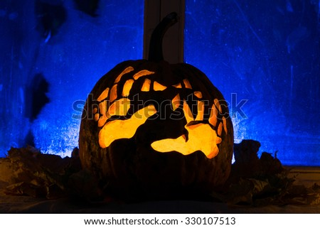 Photo for a holiday Halloween, pumpkin with hands against an old window with autumn leaves - stock photo