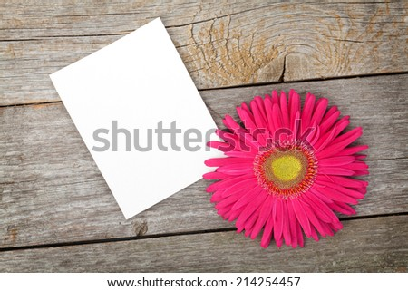 Photo frame and gerbera flower over wooden table background - stock photo