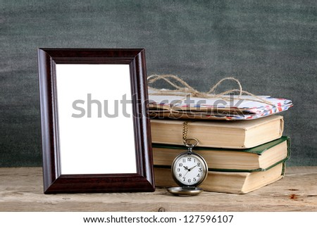 Photo frame and pile of old books on wooden table - stock photo