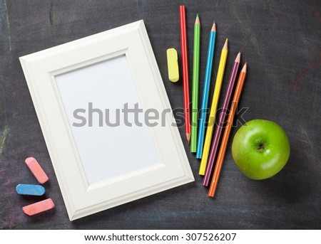 Photo frame and school supplies on blackboard background. Top view with copy space - stock photo