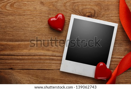 Photo frame and small red hearts on old wood background - stock photo