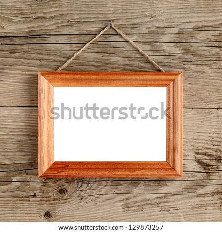Photo frame hanging on old wooden wall - stock photo