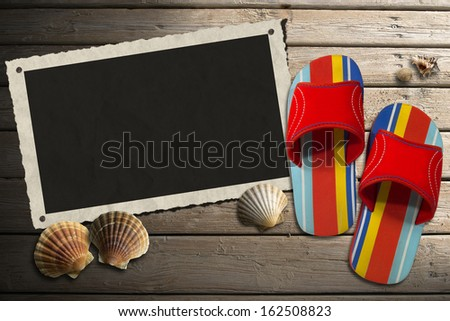Photo Frame on Wooden Boardwalk with Sand / Aged photo frame with seashells on beach, colored sandals on wooden floor with sand - stock photo