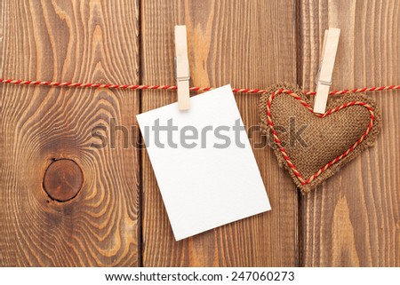 Photo frame or greeting card and handmaded valentines day toy heart over wooden background - stock photo