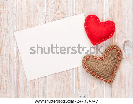 Photo frame or greeting card and handmaded valentines day toy hearts over white wooden background - stock photo