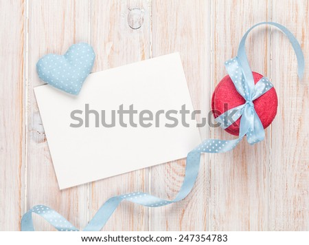Photo frame or greeting card, macarons and handmaded valentines day toy heart over white wooden background - stock photo