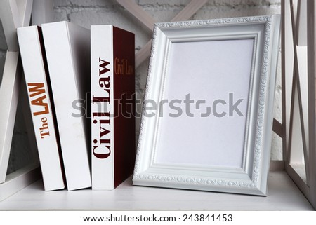 Photo frame with books on shelf, on brick wall background - stock photo