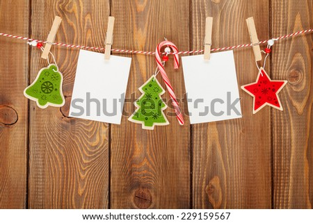 Photo frames and christmas decor on rope over rustic wooden board with copy space - stock photo