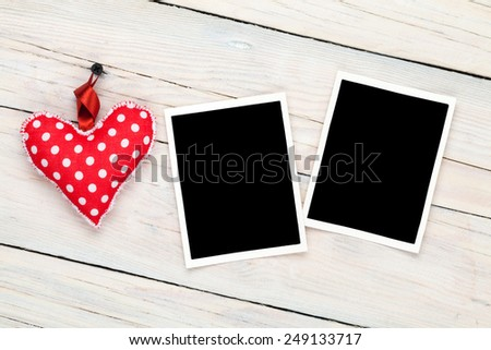 Photo frames and handmaded valentines day toy heart over wooden background - stock photo