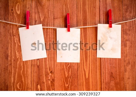 Photo  frames hanging on a rope over wooden background - stock photo