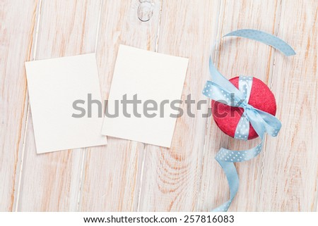 Photo frames or greeting cards and macarons with ribbon over white wooden background - stock photo